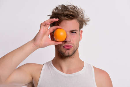 Diet and healthy lifestyle concept. Man with orange covering eye Reklamní fotografie