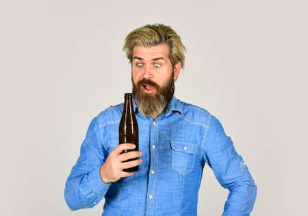 Adding a joy in Life. mature man drink beer. healthy water in glass bottle. brutal hipster drinking alcohol beverage. beer and football. relax after work day. lets have fun. bearded man has hangover