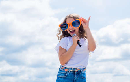 Drift into the music. karaoke club. music is my life. kid sing with mic. cheerful event manager. child have fun on party. happy singer with microphone. girl singing. vocal school concept Archivio Fotografico