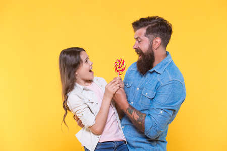 Happy family dad and daughter eat lollipop yellow background, share with me concept