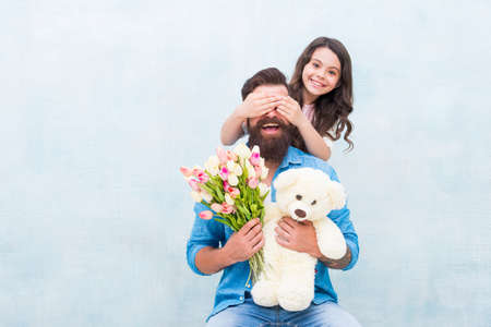 Guess who. Happy daughter clothes fathers eyes with hands. Playing guessing game. Birthday surprise. Surprise gift. Floral shop. Toyshop. Happy family. Spring holiday. Surprise concept, copy space