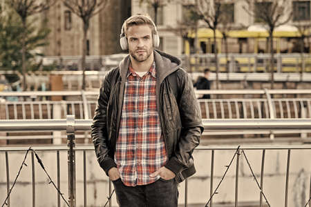 Tourist hipster with backpack headphones. Self improve. Handsome man enjoy music urban background. Distance education. Modern education. Podcast for youth. Online education courses. Listen music
