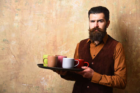 Waiter with tea cups on tray. Barman with serious face