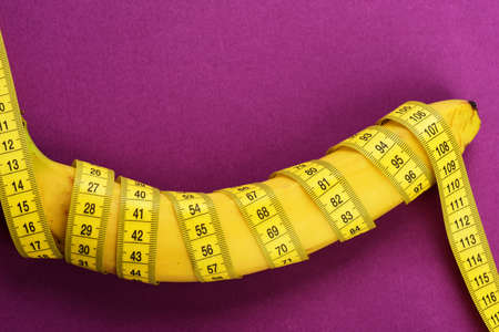 Yellow tape around banana isolated on violet background. 写真素材