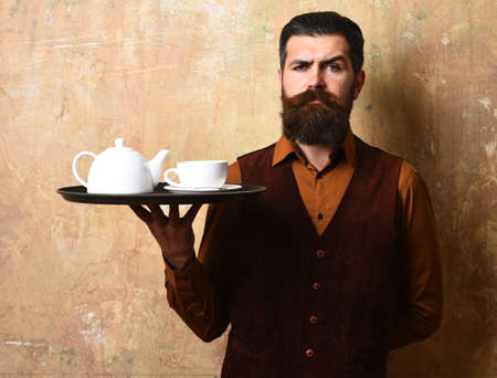 Man with beard and mustache holds tea on beige wall