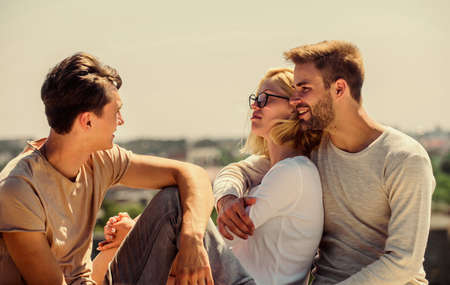Friends relaxing on roof. Carefree friends. True friendship. Being sincere with closest people. Men and woman talking sky background. Spending time with friends. Summer vacation. Discussing ideas Standard-Bild