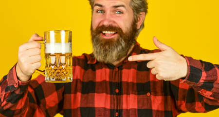 strong drink in supermarket. Beer with foam. brutal hipster drink beer. mature bearded barman hold beer glass. confident bartender raising toast. leisure and celebration. Man drinking beer in pub bar
