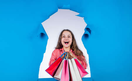 happy kid go shopping. teen girl carry heavy shopping bags. presents in packages. big sale offer. school market sale began. real shopaholic. concept of black friday. final sell-out Stock Photo