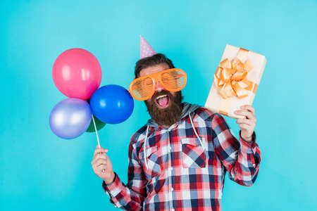 Going for shopping. hipster smiling with balloon. Celebrating happy party. Party Elements and holiday objects. Multi colored fun. best party for retirement. cheerful man with beard hold present