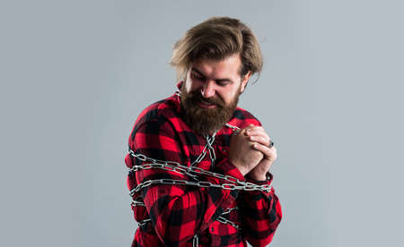 There is always a way out. sense of freedom. caucasian man with powerful metal chain on body. handsome man with beard hold chain. concept of freedom. man chained problems. liberation from slavery Stock Photo