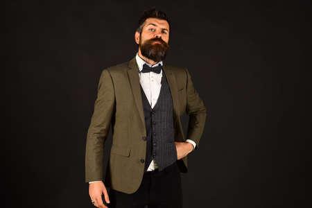Man in retro smart suit and vest on brown background. Archivio Fotografico