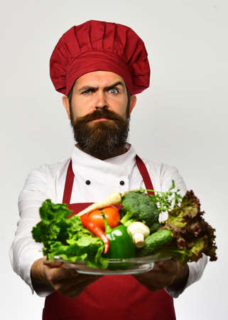 Healthy nutrition and cuisine concept. Chef holds bowl with vegetables