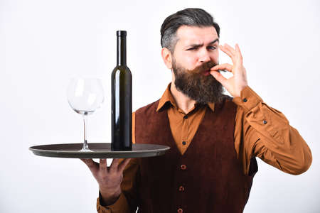 Barman serves red wine showing perfect taste sign.