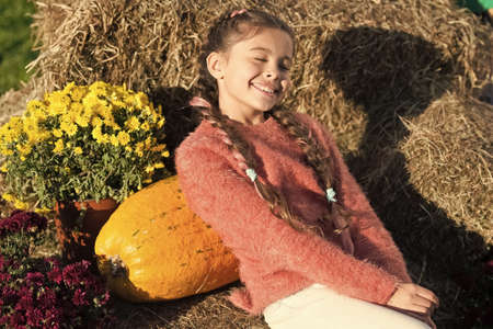 Thinking about. small girl big pumpkin. ready for halloween. autumn time. cheerful kid dried flower. fall composition. what can be cooked from zucchini. autumn rich in harvest. harvest season Banco de Imagens