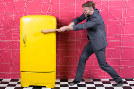 Man formal elegant suit beat with wooden bat retro vintage yellow refrigerator. Bachelor hungry want eat near fridge. Bright fridge household appliances. Hunger and appetite. Hungry attack concept