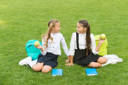 School friends relaxing after classes at school yard, school break concept