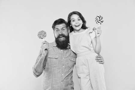 Loving daddy and small girl eating lollipop. Summer vacation. Happy holidays. Sweet childhood. When children seem hard to please. Daughter and father eat sweet candy. Bearded man and cute sweet baby Imagens