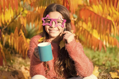 Aint it funny. I love smell of autumn leaves in morning. Happy little child hold coffee cup on autumn morning. Small girl drink morning coffee or tea. Good morning fun 写真素材