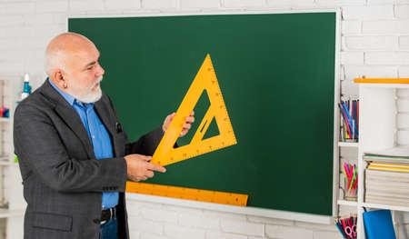 Maths Problem Solving. senior man teacher use math triangle tool. bearded tutor man at blackboard. back to school. Math science concept with school lesson items. Mathematics at chalkboard