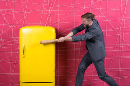 By force or persuasion. man in stylish jacket. confident businessman in suit. Businessman with bat hit yellow fridge. angry man. Feel the success. Business fashion. Male formal fashion