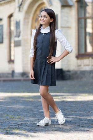 My uniform as functional as fashionable. Happy kid wear uniform in schoolyard outdoors. Schoolwear trend. Clothing standards. Dress code. School fashion. Formal education. Back to school. September 1