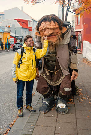 Reykjavik, Iceland - October 12, 2017: man tourist picking nose of troll figure. Happy man with clay figure of troll. Tourist attraction. Popular tourist destination. Hes my lucky troll Sajtókép