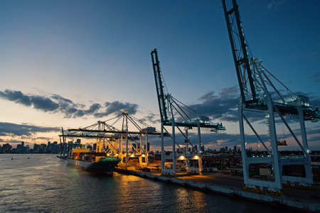Miami, USA - March 01, 2016: freight carrier and cranes on evening sky. Cargo carrier on pier side. City skyline at dusk. Shipping and shipment. Cargo loading Sajtókép