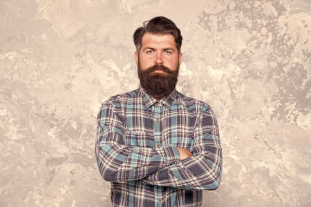 Individual style. Barber salon. Hipster with beard and mustache wear blue shirt. Grooming service concept. Well groomed macho. Handsome hipster man on grey wall background. Bearded man hipster style