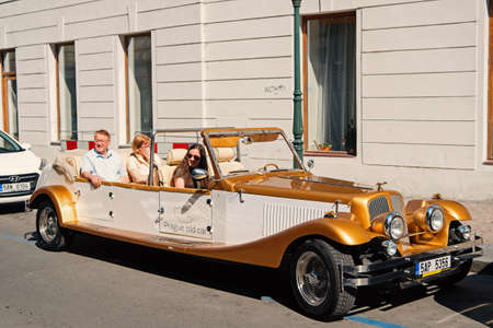 Prague, Czech Republic - June 03, 2017: travelers sit in old car. Vintage vehicle parked at street. Historical destination. Sightseeing tour. Seeing city landmarks. Travel and trip. Classic transport