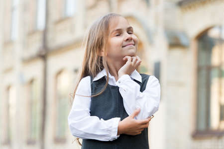 Happy pensive kid think positive with closed eyes and back to school look in formal uniform outdoors, imagination
