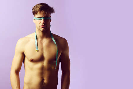 Naked man with tape for measuring tied on his eyes 免版税图像 - 157890686