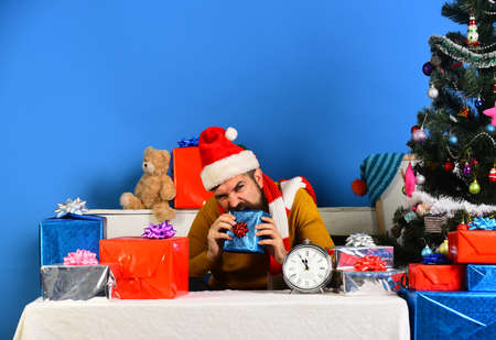 Happy man in Christmas Santa hat trying to bite present