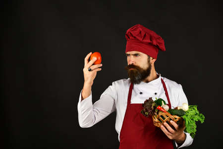 Man with beard on black background looks at tomato.