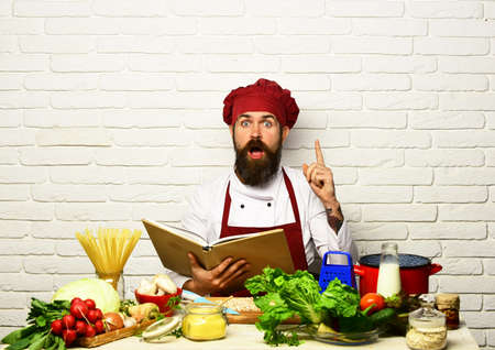 Chef prepares meal. Man with beard holds cook book