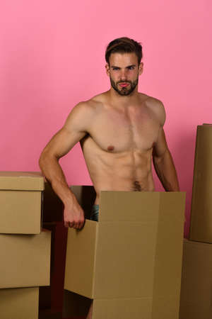 Man with naked body hiding in cardboard box