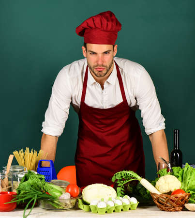 Cook works in kitchen near table with vegetables and tools Zdjęcie Seryjne