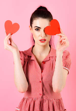 Sexy girl concept. Sexy girl with make up holding red hearts