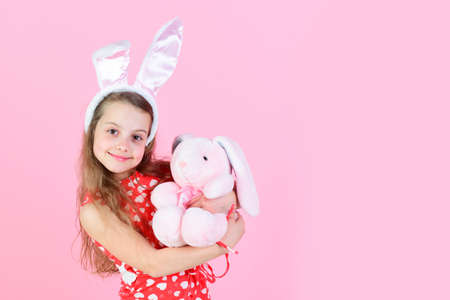 Fertility and new life concept Happy girl holding rabbit toy on pink background, copy space