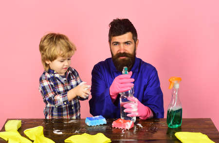 Guy with beard and mustache with rubber glove holds spray.