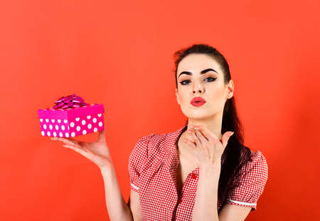 Air kiss concept. Woman holds bright pink gift pack and sends air kiss. Stok Fotoğraf