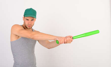 Guy in grey tank top holds bright green bat 스톡 콘텐츠