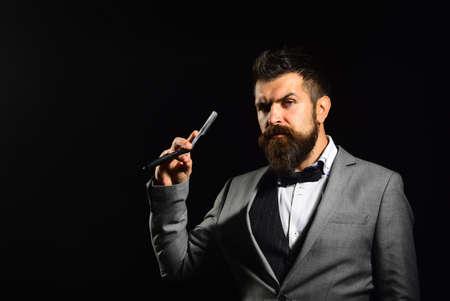 Man with long beard holds blade for razor. Barbershop advertising 免版税图像 - 157890774