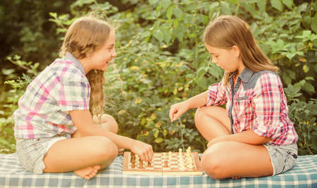my turn. worthy opponents. develop hidden abilities. two concentrated girls play chess. chess playing sisters. skilled children. turn on your brain. make the brain work. early childhood development 写真素材