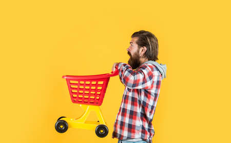 Riding a shopping cart. funny man with small shopping cart. weekend on buying products. rejoices successful purchases. brutal mature hipster go shopping. Its time to fill the cart. man go shopping Stock fotó - 154598968