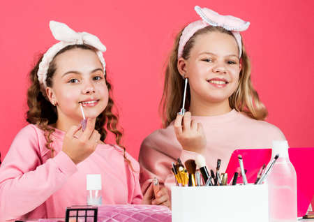 Beauty salon. Sisterhood happiness. Skin care. Kids makeup. Beauty and fashion. Happy girls doing makeup. Sisters play with cosmetics. Cosmetics shop. Hobby and fun. Cosmetics for children. Spa party Standard-Bild