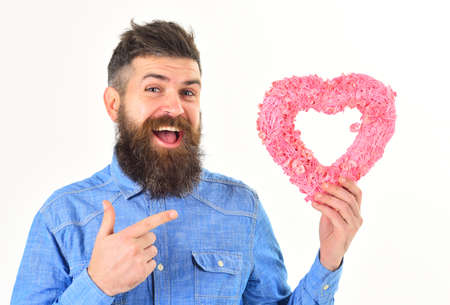 Hipster in denim shirt points on pink heart with finger.
