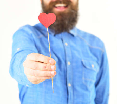 Love heart concept. Man in stylish shirt holds little red love heart on stick. Banco de Imagens