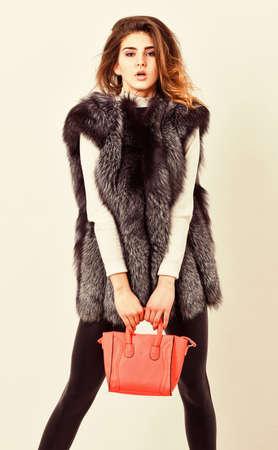 Fashion and shopping concept. Female fashion model hold purse. Woman in fur coat with handbag on white background. Girl fashion lady stylish hairstyle wear mink fur coat. Fashion stylish accessory