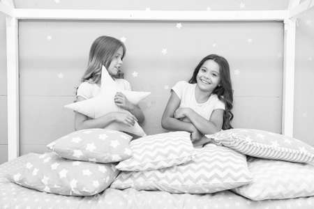 Happy childhood. Happy children have fun in bed. Little girls play with cushions. Enjoying childhood years. Childhood protection. Childcare center. Childrens day. Childhood only happens once