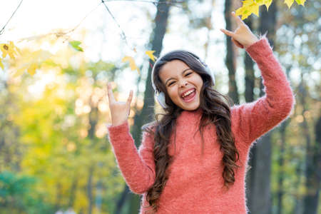 going crazy. child listen music in fall forest. enjoy elearning in headset. kid wear sweater in autumn park. happy kid relax in autumn nature. small girl wear headphones. modern school education Stockfoto